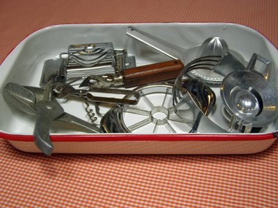 A shallow container holds kitchen tools.