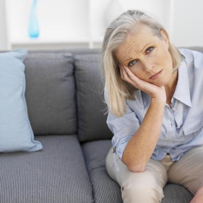 Mature woman sitting down on a couch looking tired.