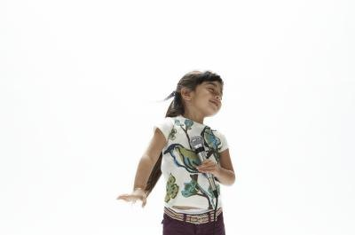 Young girl stops after the music stops while dancing.