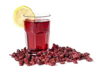 Cranberries surrounding a glass of cranberry juice with a lemon slice