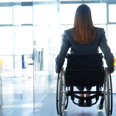 Rearview of a business woman in a wheelchair.