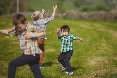 3 young boys dancing outdoors.