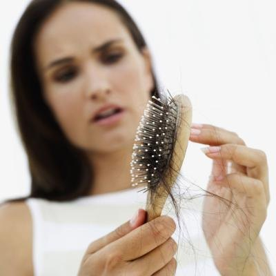 Woman looking at brush full of hair.