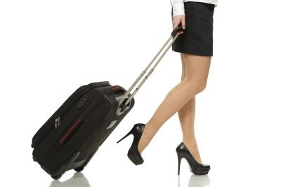Business woman's legs with a suitcase with a handle.