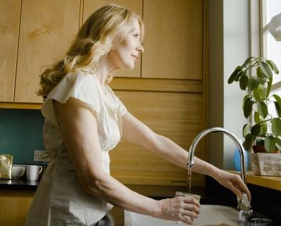 Woman pouring glass of water from sink and looking out window.
