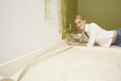 Woman painting wall; white baseboard.
