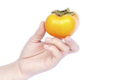 Hand holding a persimmon.