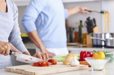 A close up of a couple cooking in a kitchen.