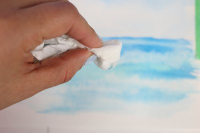 A paper towel absorbs wet paint to form clouds in the sky.