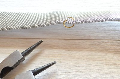 Carefully slide the jump ring through the mesh chain.