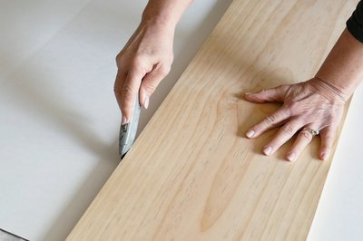 Score the white cardboards to the width of the wood board
