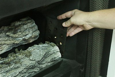 Hide the smoker box behind the logs or on the sides.