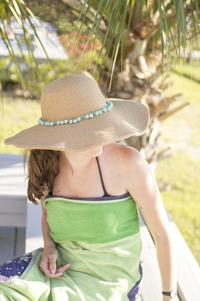 Enjoy the look of a custom pompom-trimmed beach hat this spring and summer.