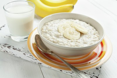 A bowl of oatmeal with sliced bananas on top