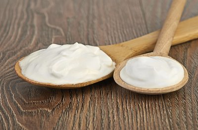 Spoonfuls of sour cream on a wooden surface