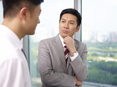 Two businessman having a conversation in an office.