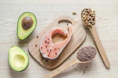 An overhead view of healthy dietary fats including salmon, avocado, nuts and seeds on a cutting board.