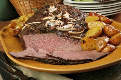 Slices of beef brisket on a plate with mushrooms and potatoes.