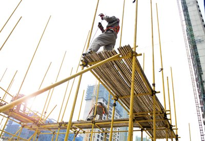 Workers on scaffolding wearing safety harnesses
