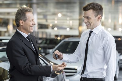A car sales person hands keys to a customer.