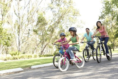A young family riding bikes in the park.