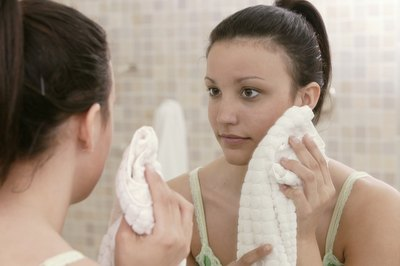 A woman looks in the mirror and dries her face with a towel.