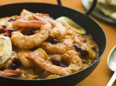 A bowl of prawns, black bean, and plantains slices on a kitchen table.