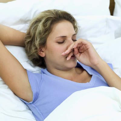Woman with a runny nose in bed