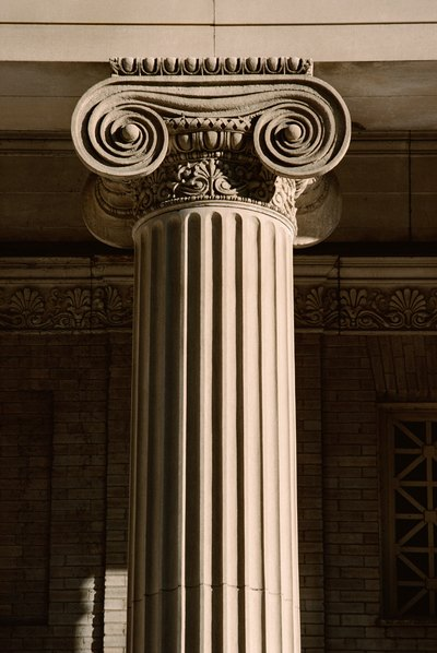 The scrollwork at the top of the column is indicative of the Ionic order.