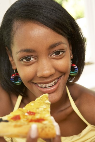 Girl with braces eating a slice of pizza