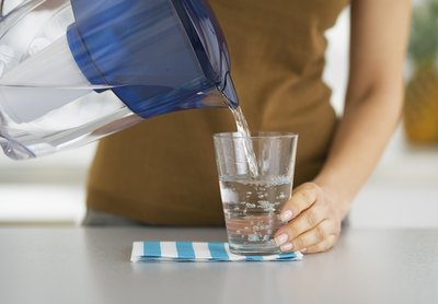 A woman pouring a glass of filtered water from a pitcher a the kitchen counter.