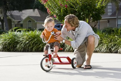 Dad helping child learn to ride a tricycle