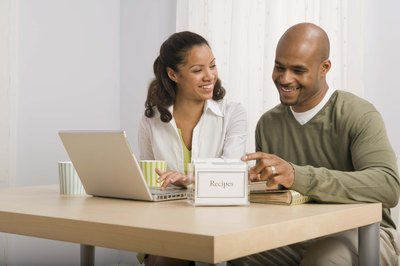 Couple looking at cookbook and laptop