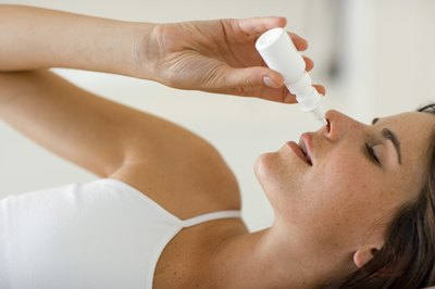 Woman using a nasal spray decongestant