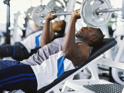 A man lifts weights at a gym.