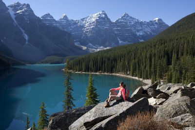 A woman hikes near a mountain lake in the Rockies.