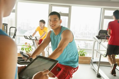 A young man is riding a stationary bike.