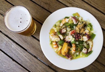 An overhead view of a seafood dish and a pint of beer.