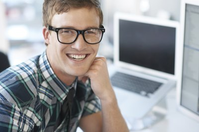 film editor smiling in front of computer