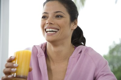 Smiling woman holds a glass of orange juice.