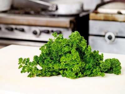 A bunch of fresh parsley on a cutting board.