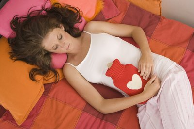 Woman with cramps, using heating pad
