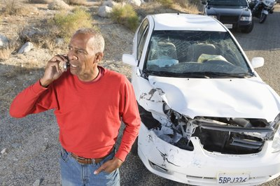 Man on phone with damaged car.