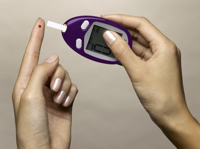 A diabetic woman takes a blood sugar reading.