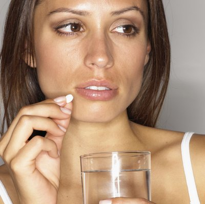 woman taking pill with water