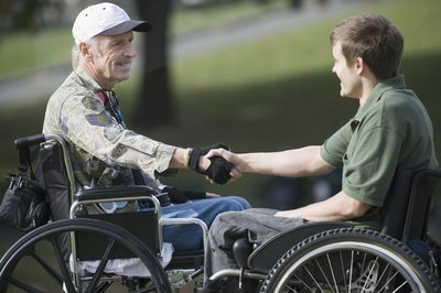 Young man in wheelchair shaking hand of veteran in wheelchair.
