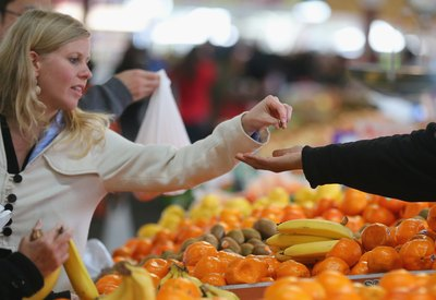 A woman purchases fruit from a vender at a market.