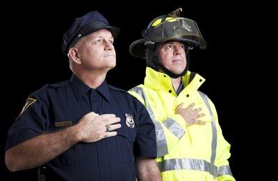 Two firemen hold their hands over their hearts while singing the U.S. national anthem