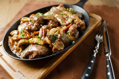 Liver baked with mushrooms and herbs in a cast iron pan.