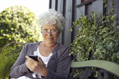 A woman uses her smart phone in the backyard.
